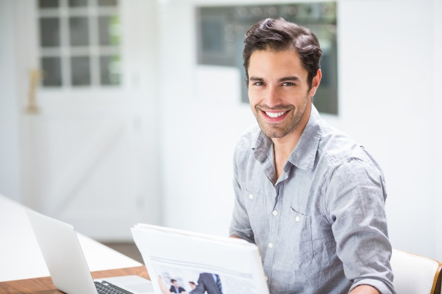 smiling-young-man-holding-documents-while-sitting-desk-with-laptop_107420-20738-359c520c